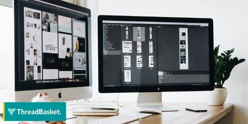 Image of 2 iMac screens standing on the work desk of a layout artist.