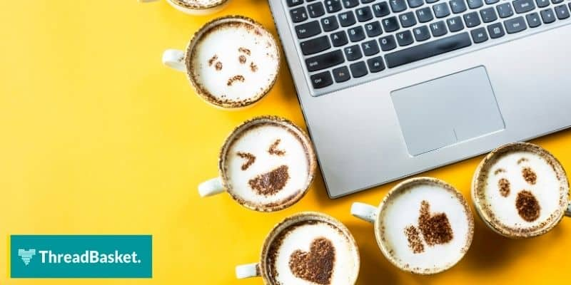 coffee cups with emojis and a laptop on the side