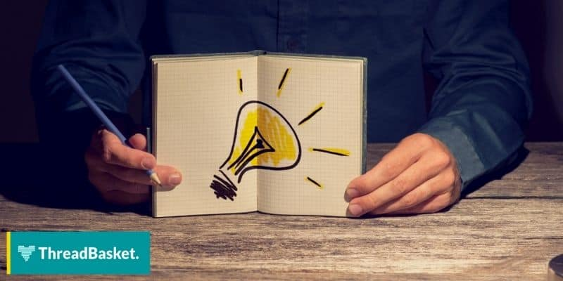 Person holding a notebook with a yellow light bulb drawing