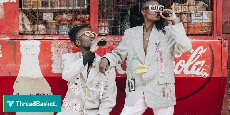Image of two fashionable black guys drinking coke outside a mini store