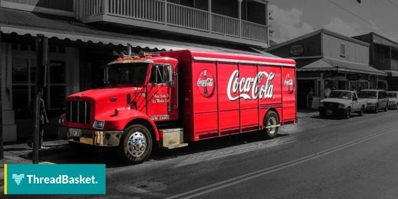 image of a read coca-cola truck on the road side on greyscale background