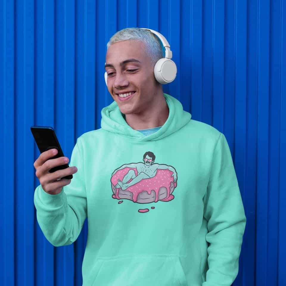 photo of a smiling man on his phone wearing a mint green hoodie with a donut bath design