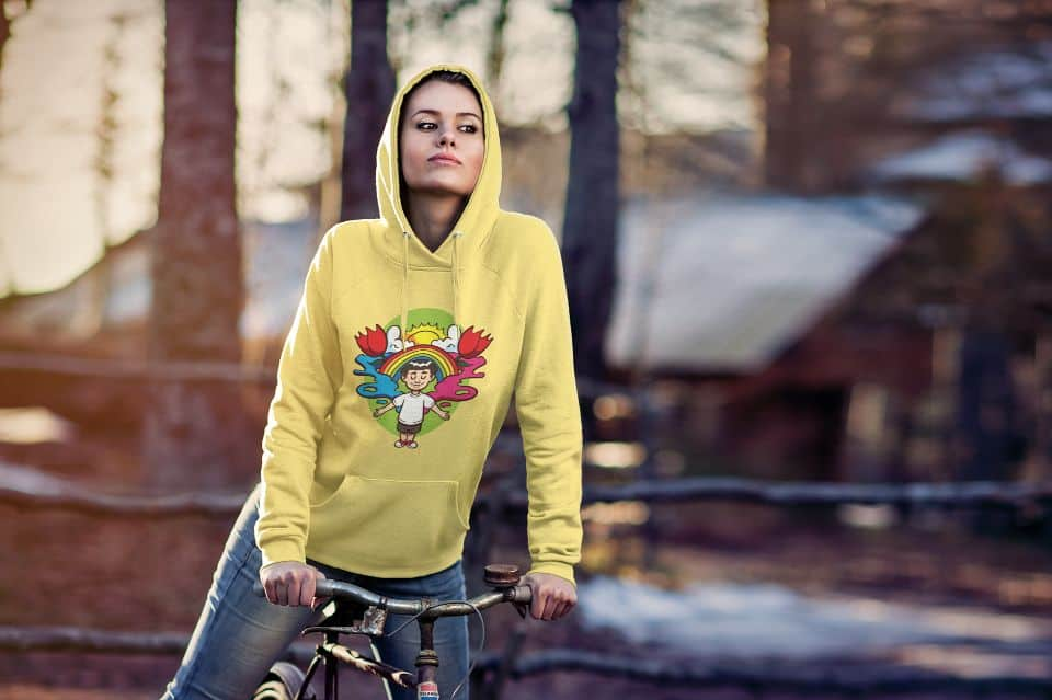 photo of a young woman riding a bike wearing a yellow hoodie with a majestic mind design