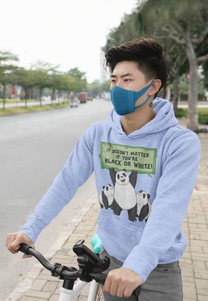 photo of a young man on a bicycle wearing a hoodie with a panda colorism design