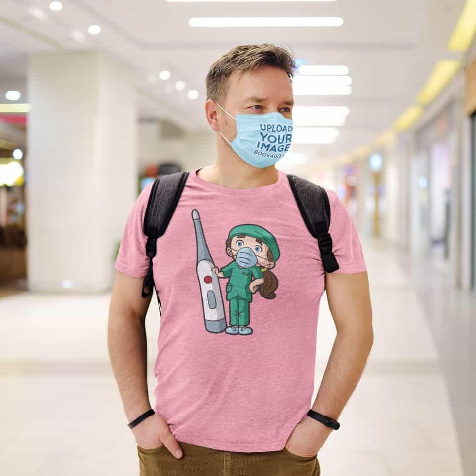 mockup of a man wearing a t shirt and a face mask at a shopping mall 45628 r el2