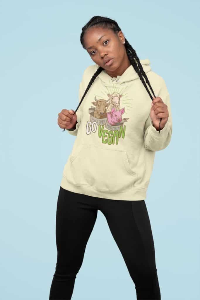 photo of a woman posing and grabbing her braids wearing a hoodie with a live peacefully go vegan design