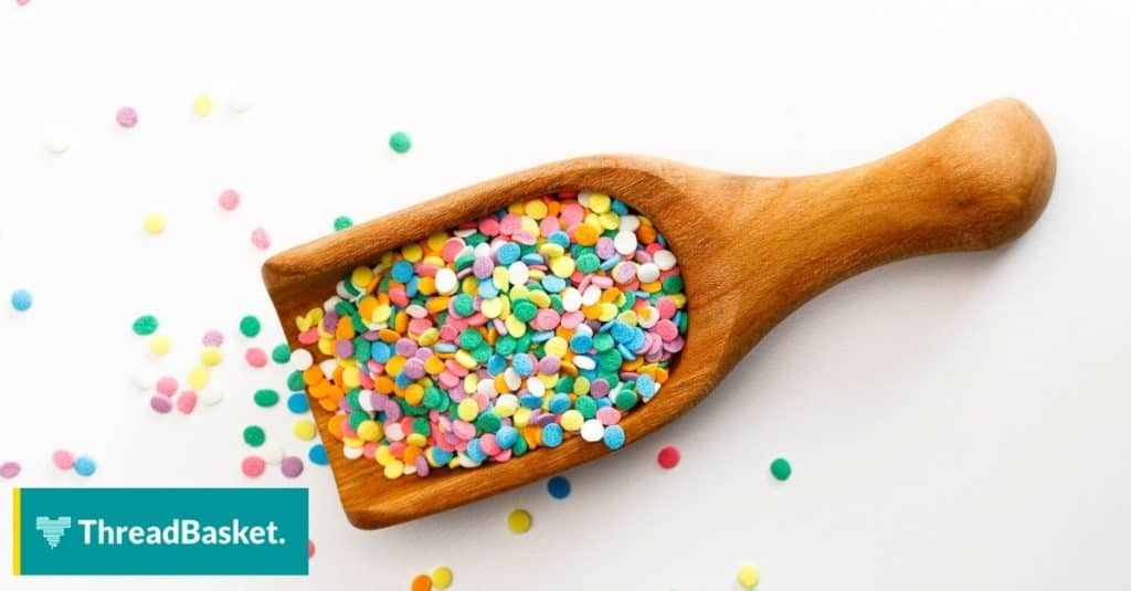 pastel colored sprinkles on small wooden scoop