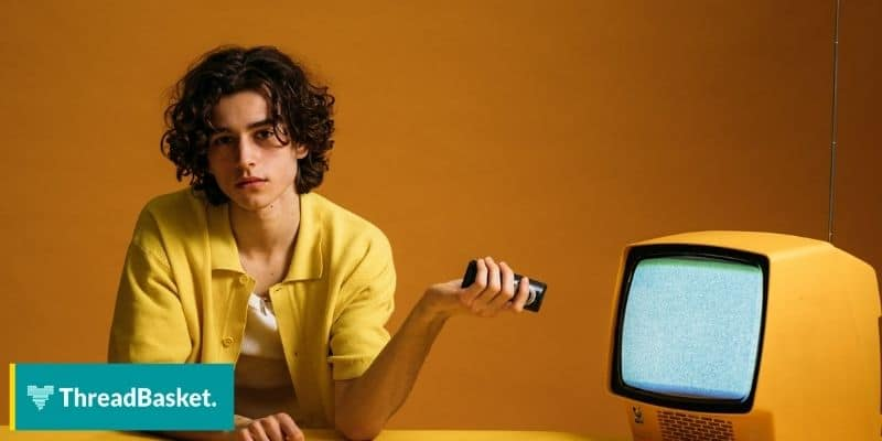 a model wearing an orange coat holding a remote pointed to an orange colored tv