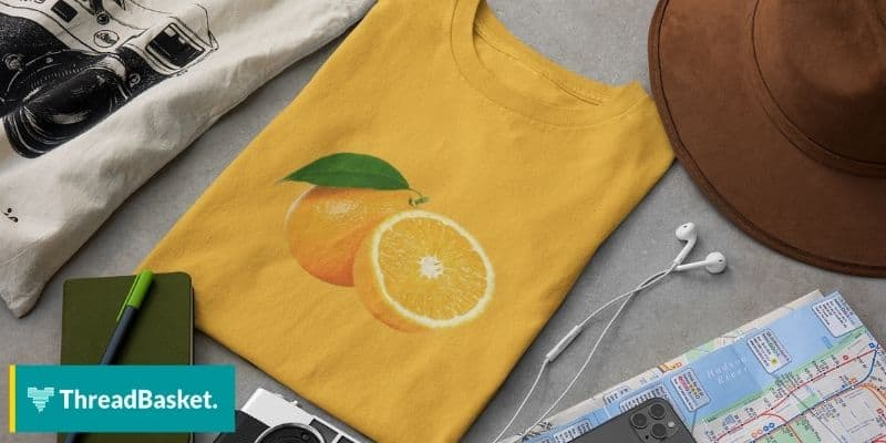 an orange colored t-shirt with an orange graphic on a table with other art materials