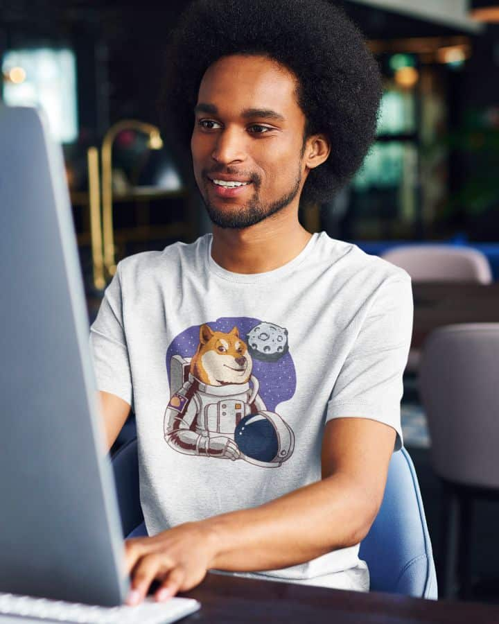 photo of a man working at an office wearing a shirt with moon meme design