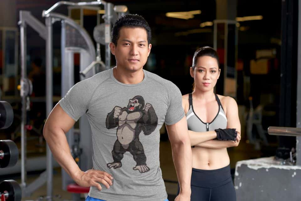 photo of a man and a woman in the gym where the guy is wearing a tee with gray chest design