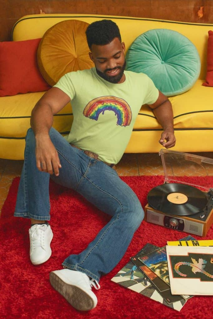 photo of a man listening to a record with a 70s aesthetic wearing a tee with sweet rainbow design