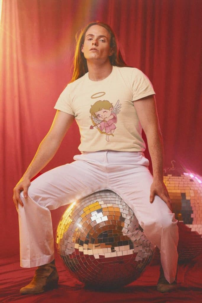 t shirt mockup of a man sitting on a discoball wearing a t shirt with cupid design