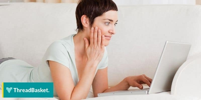 woman on couch resting while using laptop with surprised face