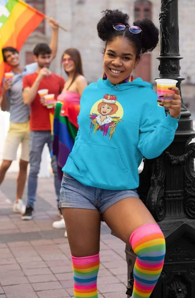 photo of a woman in an lgbt parade wearing a hoodie with a rainbow queen design