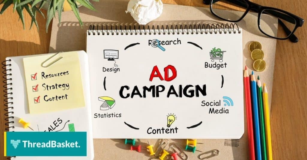 image of a desk with office suppliers and a notebook that says ad campaign