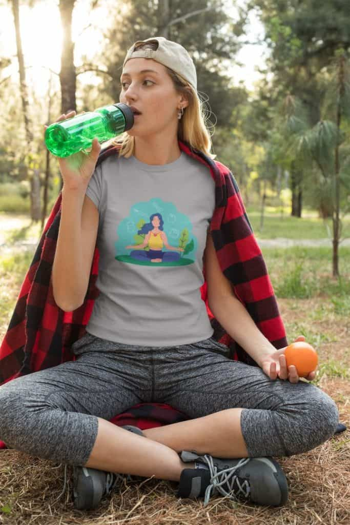 photo of a woman at the park drinking water wearing a shirt with a naturally zen design