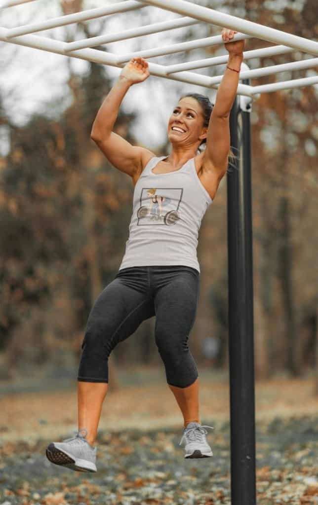 photo of a strong woman crossing a monkey bar wearing a tank top with the fitspiration design