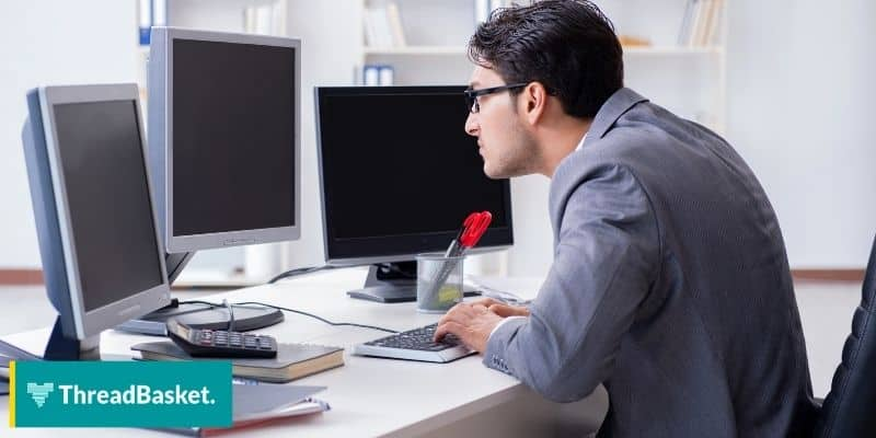 guy with glasses using multiple computers