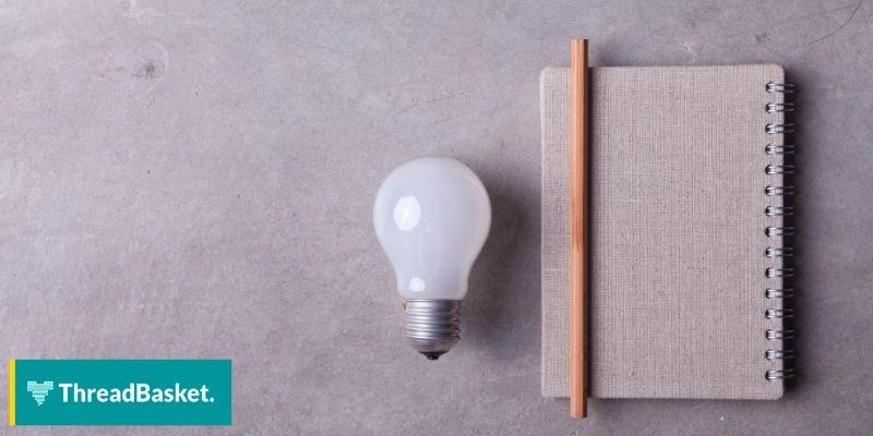 image of a brown notebook beside a light bulb