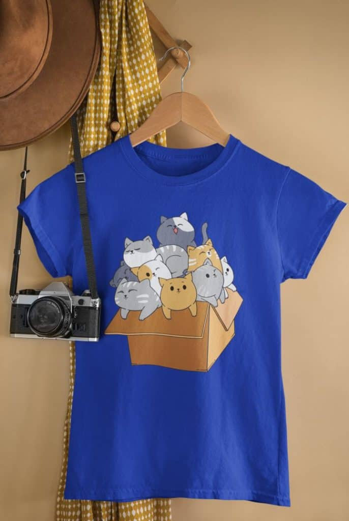 mockup of a t shirt hanging by a vintage camera