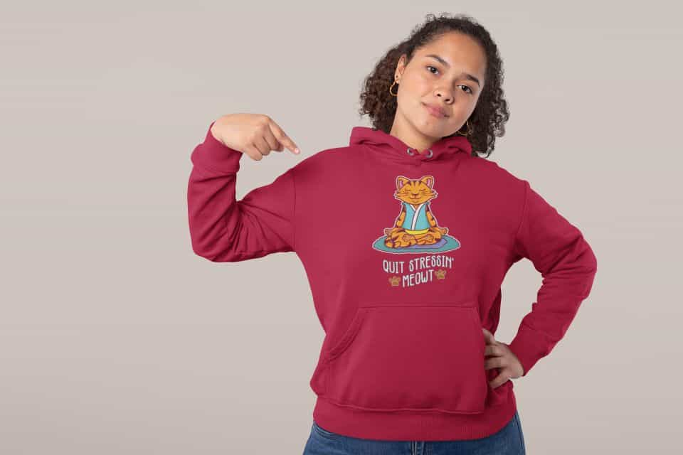 studio mockup of a confident woman pointing at her hoodie