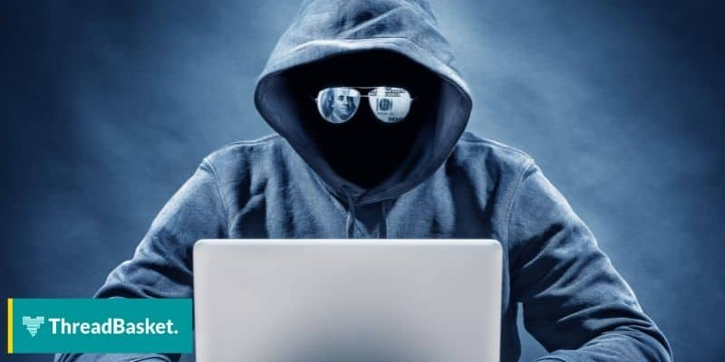 suspicious man hacker wearing hoodie and shade in front of laptop