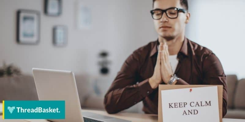 person trying to be calm in front on his computer witt keep calm sign on his table